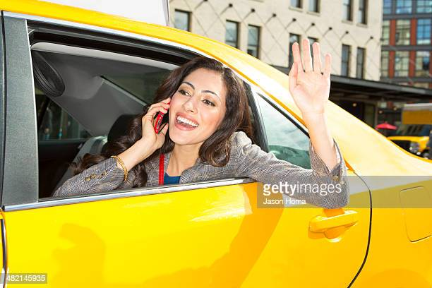 Mixed race woman waving from taxi
