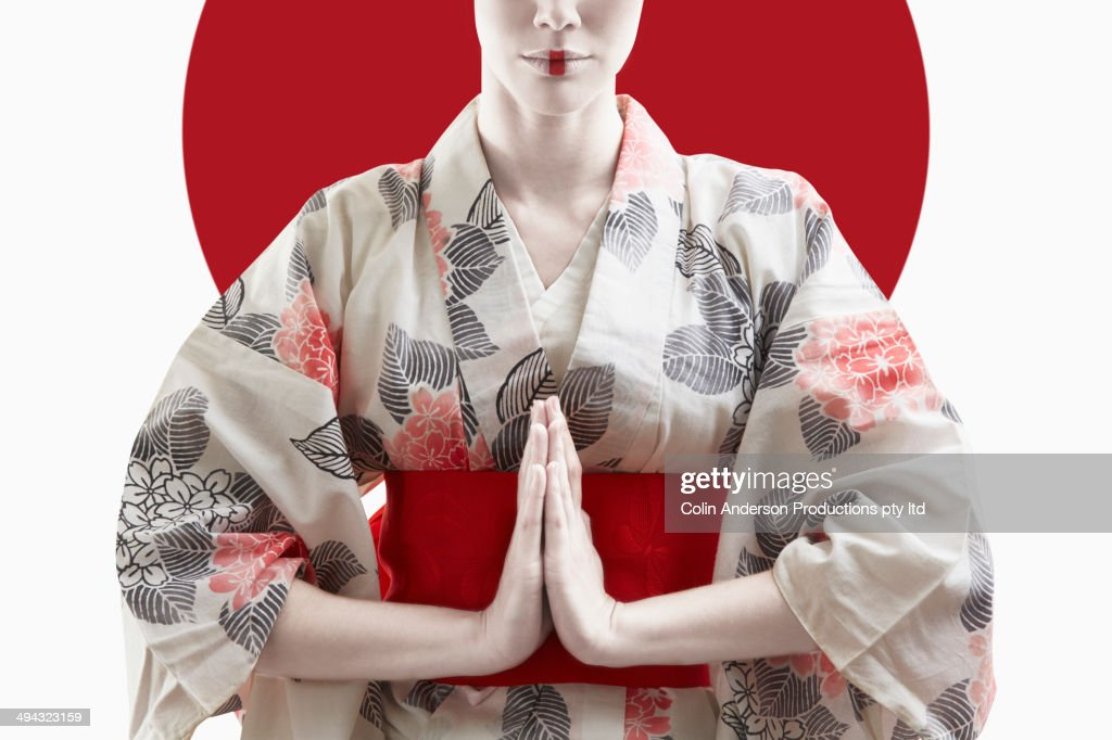 Mixed race woman wearing kimono in front of Japanese flag
