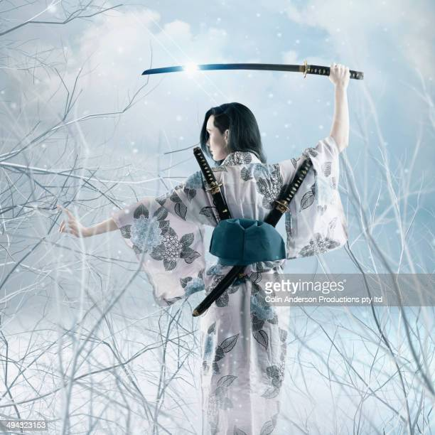 Mixed race woman wielding sword in kimono