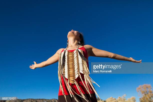Mixed race woman with arms outstretched in desert