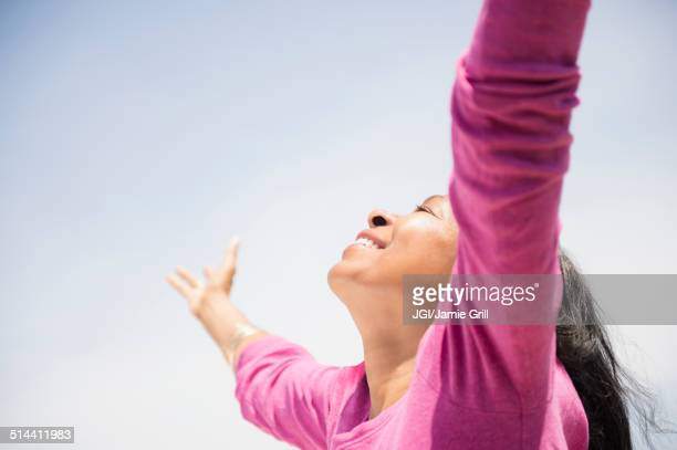 Mixed race woman with arms outstretched outdoors