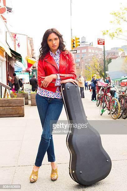 Mixed race woman with guitar case on city sidewalk