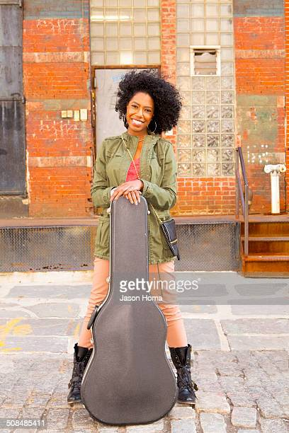 Mixed race woman with guitar case on city street