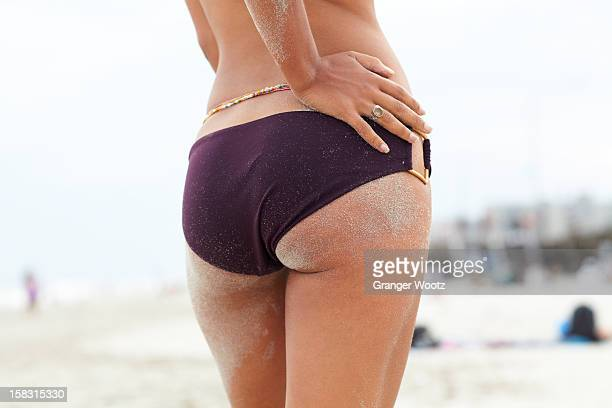 Mixed race woman with sand on her buttocks