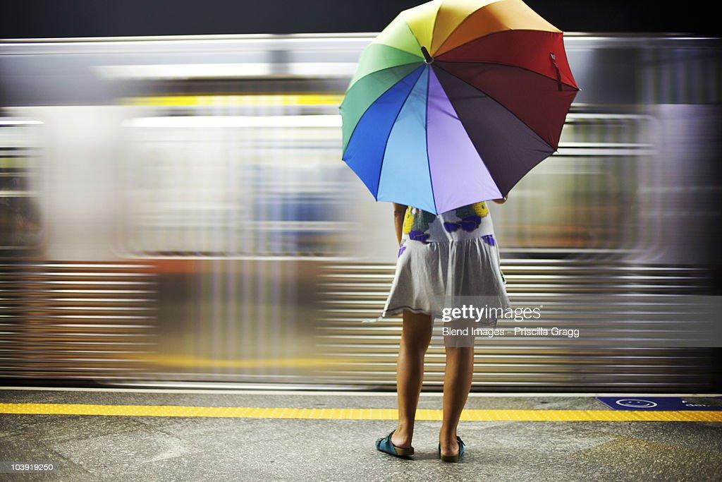 Mixed race woman with umbrella on train platform : Stock Photo