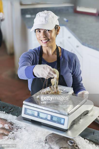 Mixed race woman working in fish market, weighing shrimp