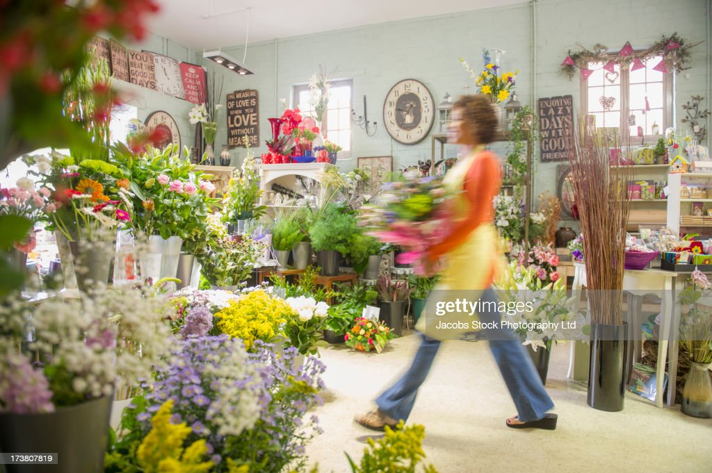 Mixed race woman working in florist shop : Stock Photo
