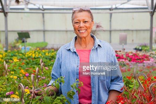 Mixed race woman working in plant nursery : Foto de stock