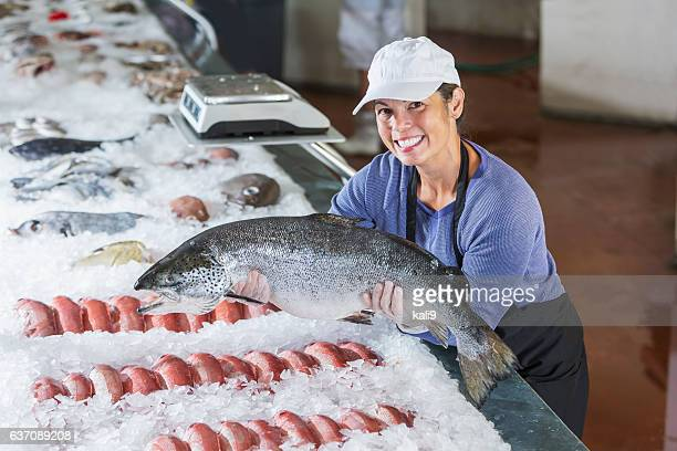 Mixed race woman working in seafood market holding fish