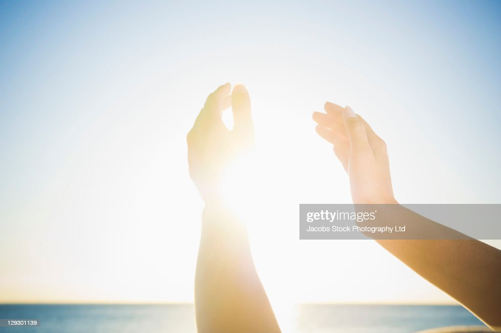 Mixed race woman's hands holding the sun : Stock Photo