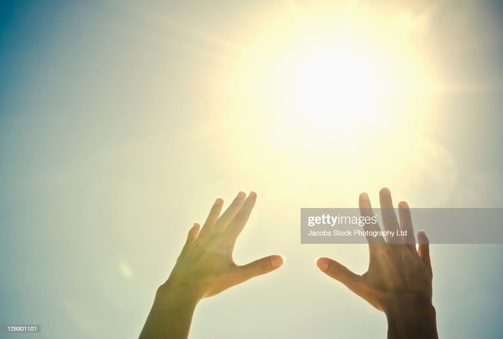 Mixed race woman's hands reaching toward sun : Stock Photo