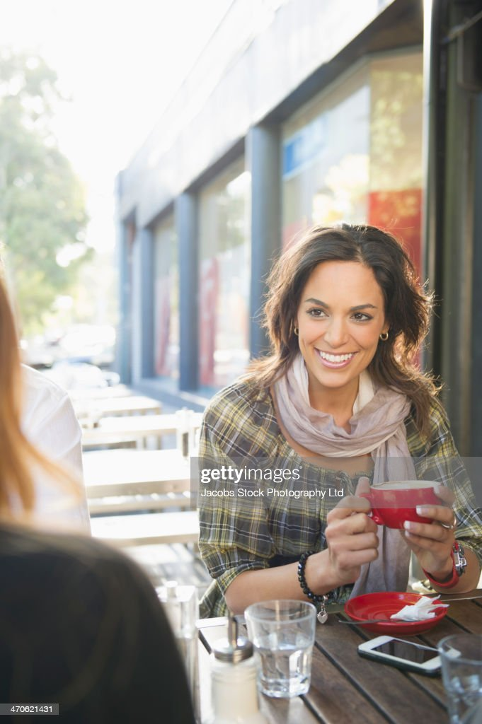 Mixed race women having coffee at sidewalk cafe