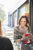 Mixed race women having coffee at sidewalk cafe
