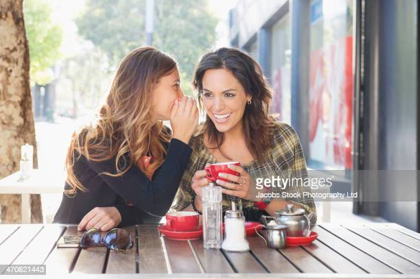 Mixed race women having tea at sidewalk cafe