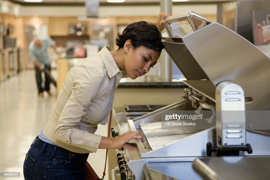 Mixed race women looking at grill in showroom : Stock Photo