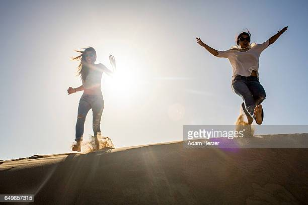 Mixed race women playing in sand dunes