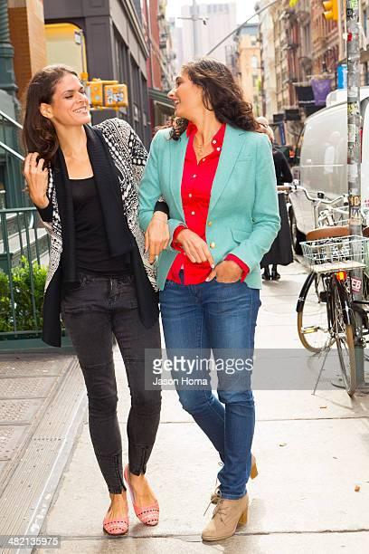 Mixed race women walking together on urban sidewalk