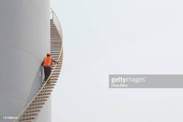 Mixed race worker climbing staircase on storage tank