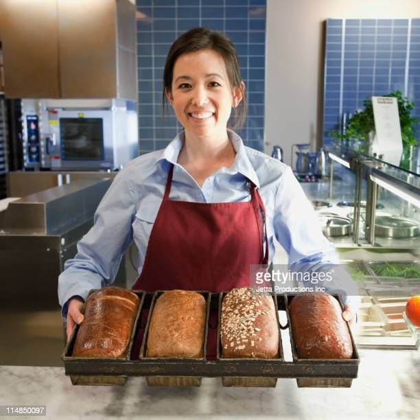 Mixed race worker holding bread in cafe