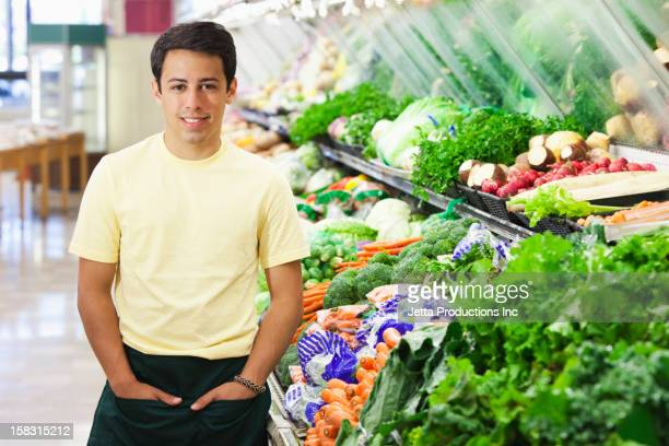 Mixed race worker in produce section of grocery store