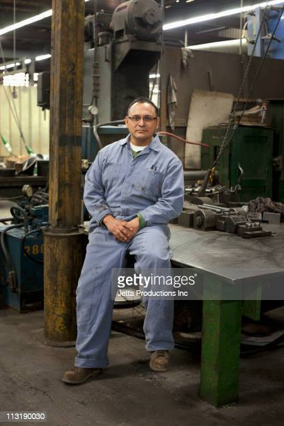 Mixed race worker sitting on table in factory