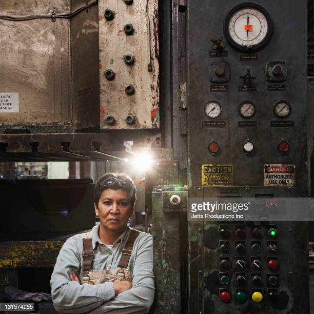 Mixed race worker standing near factory control panel