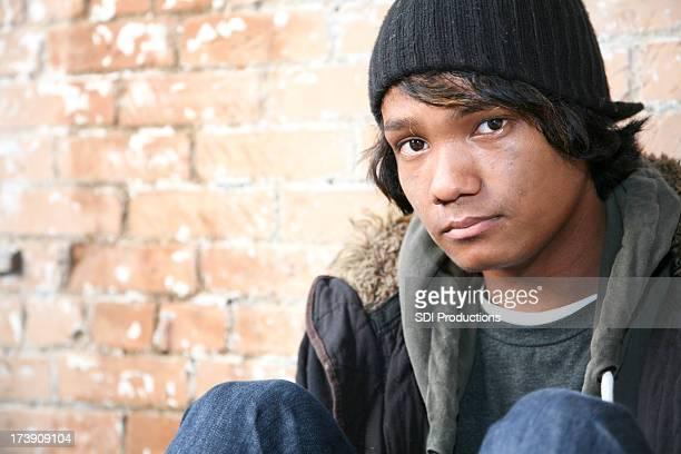 Mixed Race Young Man at Brick Wall with Copy Space