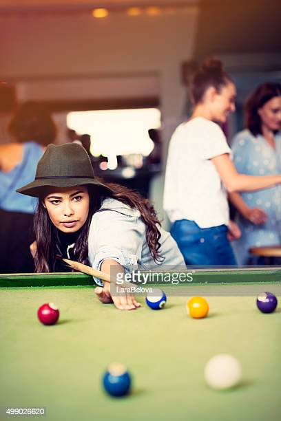 Mixed race young woman playing pool game in pub