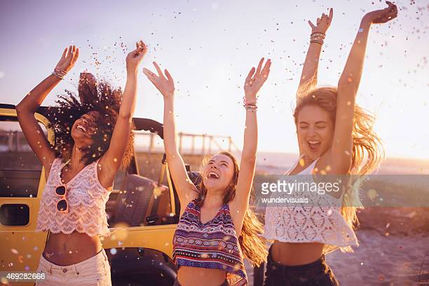 Mixed racial group dancing on a beach with confetti