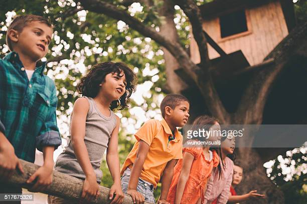 Mixed racial group of children standing on a fence