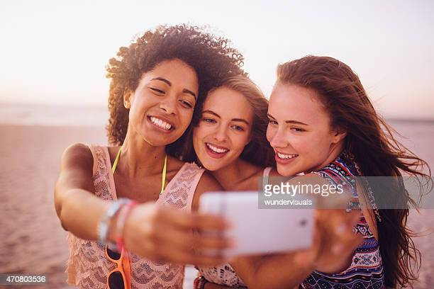 Mixed racial group of girls taking a selfie on beach