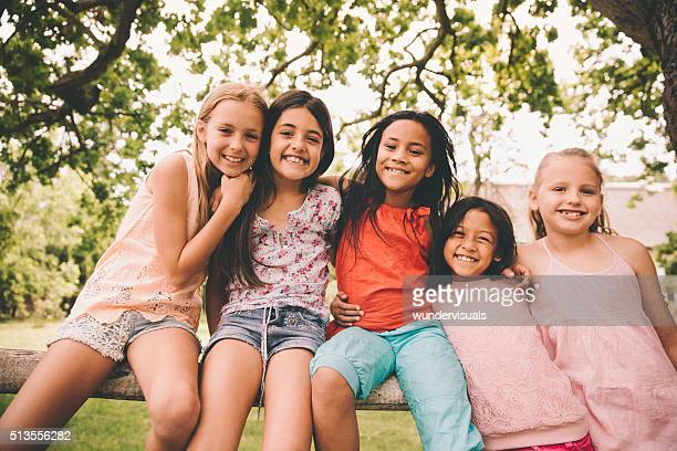 Mixed racial group of little girls smiling together in park