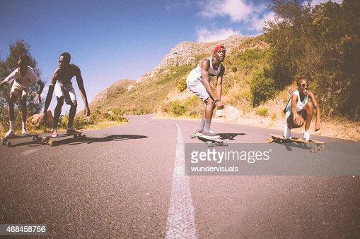 Groupe de teen multiraciale mixte des skateurs courses de descente tous ensemble