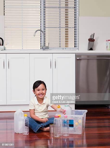 Mixed Rae girl filling recycling bin