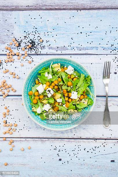 Mixed raw salad with roasted chickpeas, feta cheese, avocado and black sesame on plate