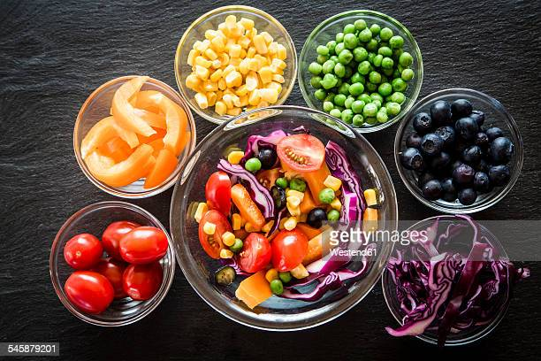 Mixed salad and glass bowls with different raw vegetables rainbow-coloured arranged on slate