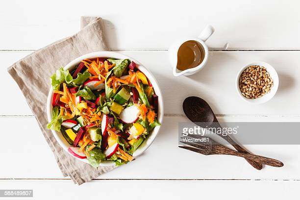 Mixed salad in bowl on wood