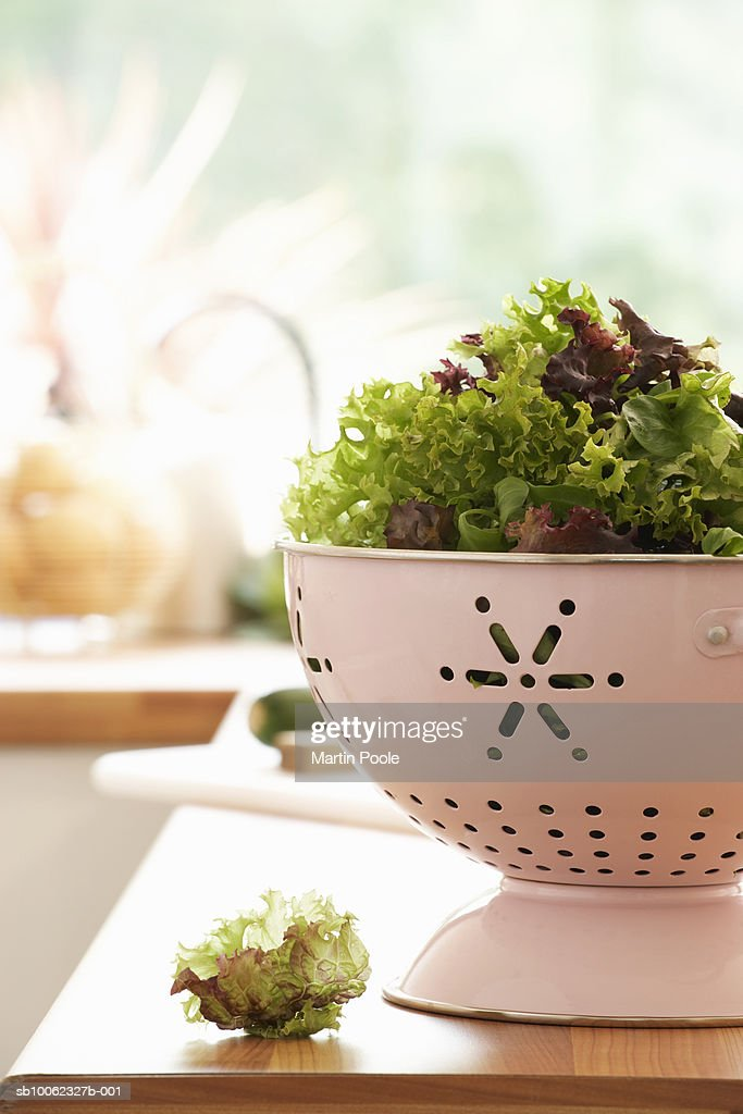 Mixed salad in colander on kitchen counter : Stock Photo