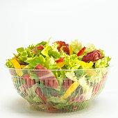 Mixed salad in plastic bowl, close-up