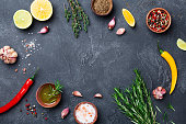Mixed spices and herbs on black stone table top view. Ingredients for cooking. Food background. Copy space for text.