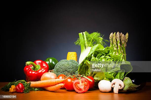 mixed vegetabales on table in front of black background