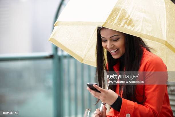 Mixed woman with umbrella text messaging on cell phone