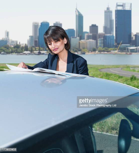 Mixed-race businesswoman reading road maps