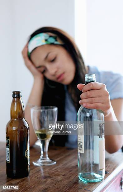 Mixed-race teenager drinking alcohol alone