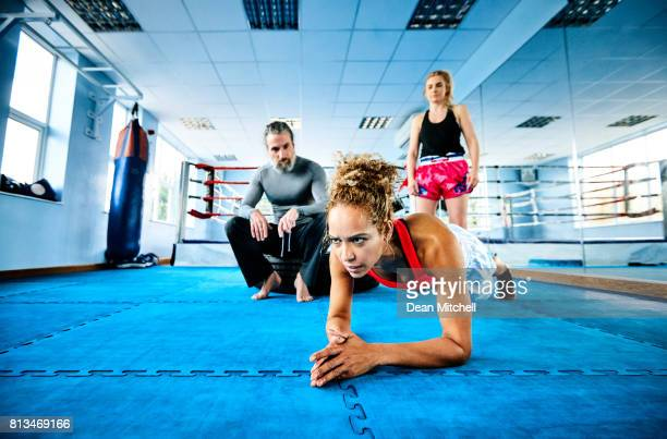 Mixedrace  woman doing push ups with fitness trainer in the gym