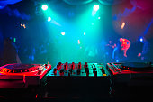 mixer and a DJ booth in the nightclub at a party with bright colorful blurred background