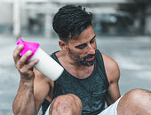 A man is sitting down to mix a protein shake after en exercise inside an abandoned warehouse.