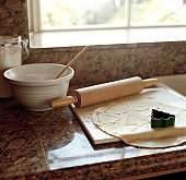 Mixing bowl, rolling pin and cookie cutter on kitchen counter