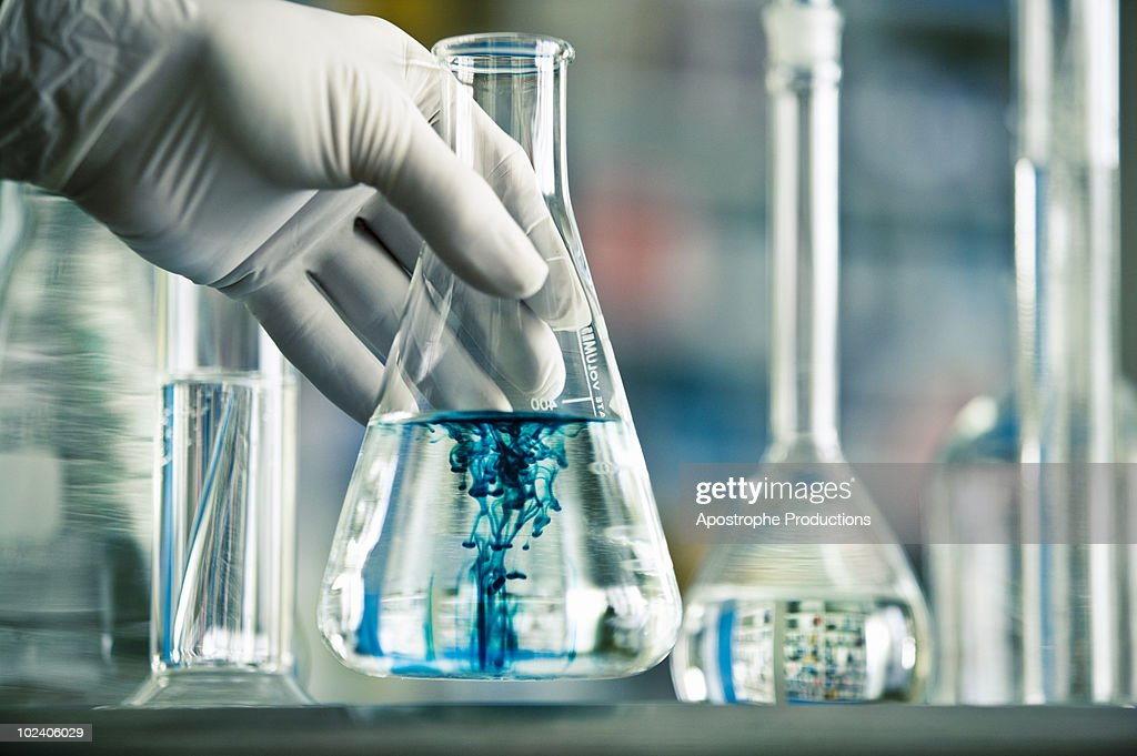 mixing of two liquids in Erlenmeyer flask : Stock Photo