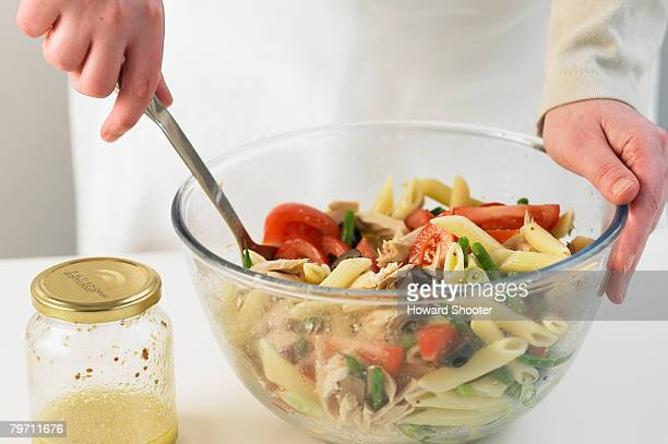 Mixing pasta salad in a glass bowl, close up